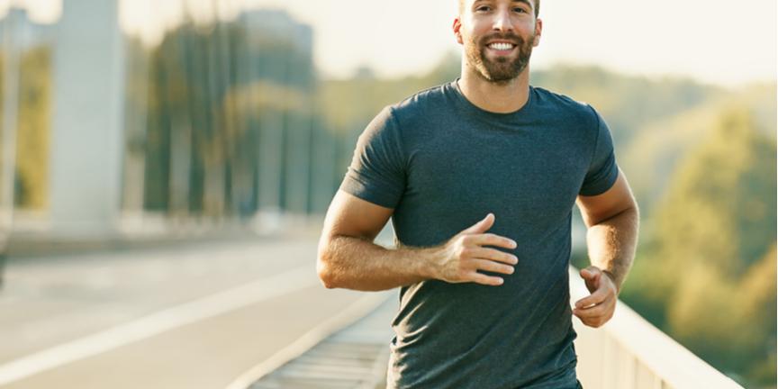 smiling-man-jogs-across-bridge