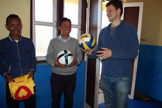 Photo: Our friend Michael handing over a football and volleyball to Dorje Sir of Chilaune school, gifts from him and Elias, another friend.