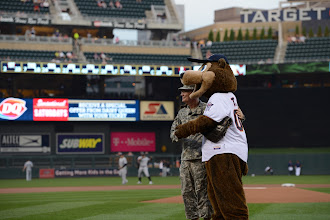 "Photo: Maj. John Donovan poses with T.C. Bear following a first-pitch strike at Target Field on Sept. 1, 2015. ""When I got to the mound all my nervousness just slipped away,"" said Donovan. ""I focused on the catcher's mitt and getting the baseball to hit that. Then I wound-up, delivered and the ball landed squarely in T.C.'s glove. He didn't have to move from his crouch to catch it – I threw a strike."" Minnesota National Guard photo by Army Staff Sgt. Patrick Loch/ Released"
