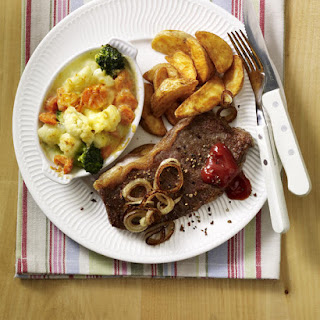 Pan Seared Steak with Vegetable Gratin and Potato Wedges.