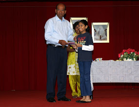 Photo: Tharani receiving a token of appreciation for recitation competition