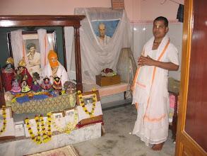 Photo: Sri Brajabandhu Brahmachari and the shrine and altar with the pictures and bigraha of Prabhu Jagadbandhu and Sri Bandhubilas Brahmachari