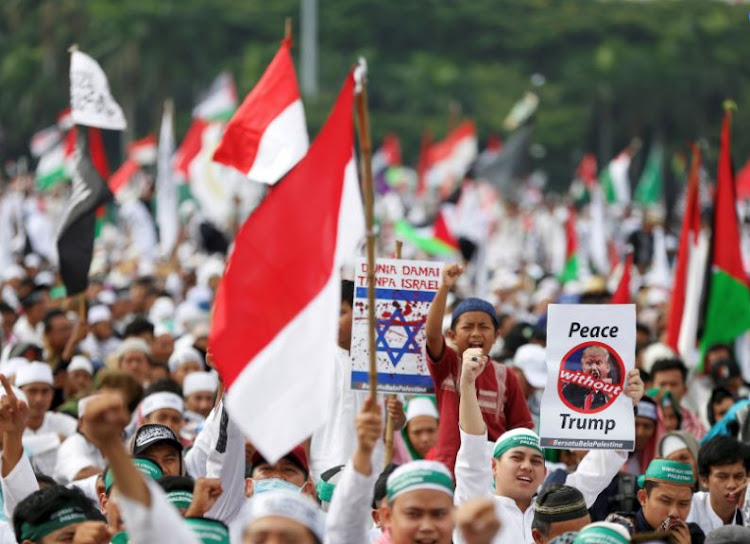 Protesters hold signs during a rally to condemn US President Donald Trumps's decision to recognise Jerusalem as Israel's capital, at Monas, the national monument, in Jakarta, Indonesia, December 17, 2017.