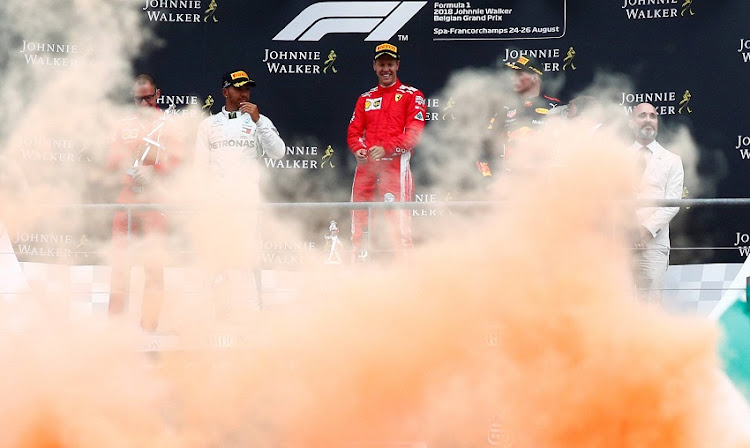 Ferrari's Sebastian Vettel celebrates on the podium after winning the race while Mercedes' Lewis Hamilton and Red Bull's Max Verstappen look on at Spa-Francorchamps, Stavelot - August 26, 2018.