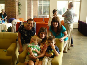 Photo: Mother with children in chair - accompanied by two Speech Therapy graduate students.-