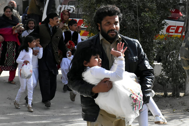 A man carries a girl as he runs out with others after gunmen attacked the Bethel Memorial Methodist Church in Quetta, Pakistan December 17, 2017.