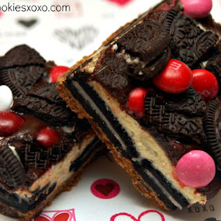 OREO CHEESECAKE BARS ON A CHOCOLATE CHIP COOKIE CRUST TOPPED WITH A CHOCOLATE GLAZE, RASPBERRY M & M'S AND MORE OREOS!