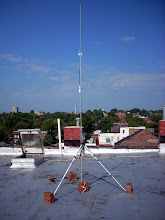 Photo: This is temporary roof tripod fashioned from a salvaged camera tripod, bricks, lots of cable ties, and electrical conduit.  This is testing out an Ubiquiti Bullet2HP access point with 12dB dipole antenna.