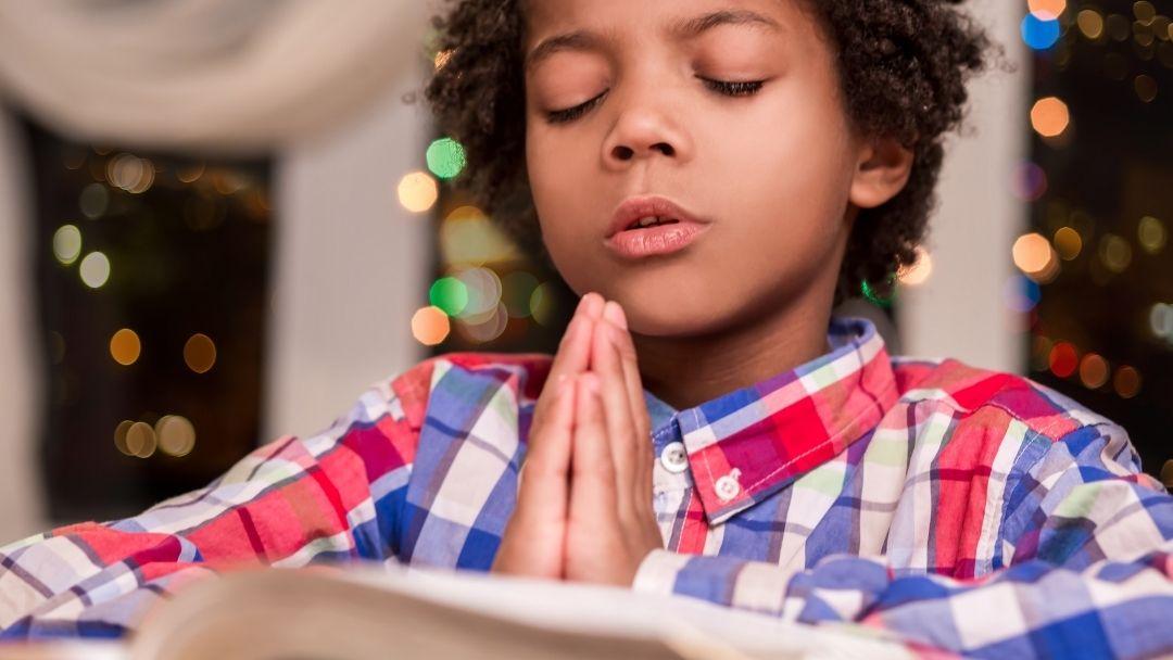 little boy praying during Holy Week