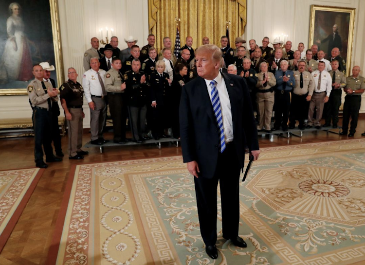 U.S. President Donald Trump approaches the news media to listen to a question about an anonymous op-ed from the New York Times after he held a gathering with sheriffs from across the U.S. in the East Room at the White House in Washington, D.C., U.S., September 5, 2018. REUTERS/Leah Millis