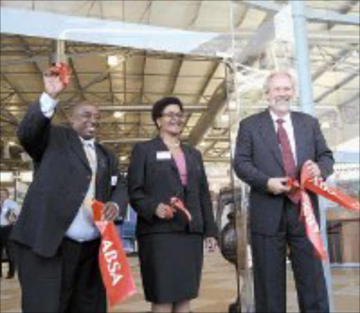 RIBBON CUTTING: International Trade Bureau executive chairman Vusi Nhlapo, Seda chief executive officer Wawa Damane and Absa Banking Services managingdirector Robert Emslie. Pic. David Bowie. © Unknown