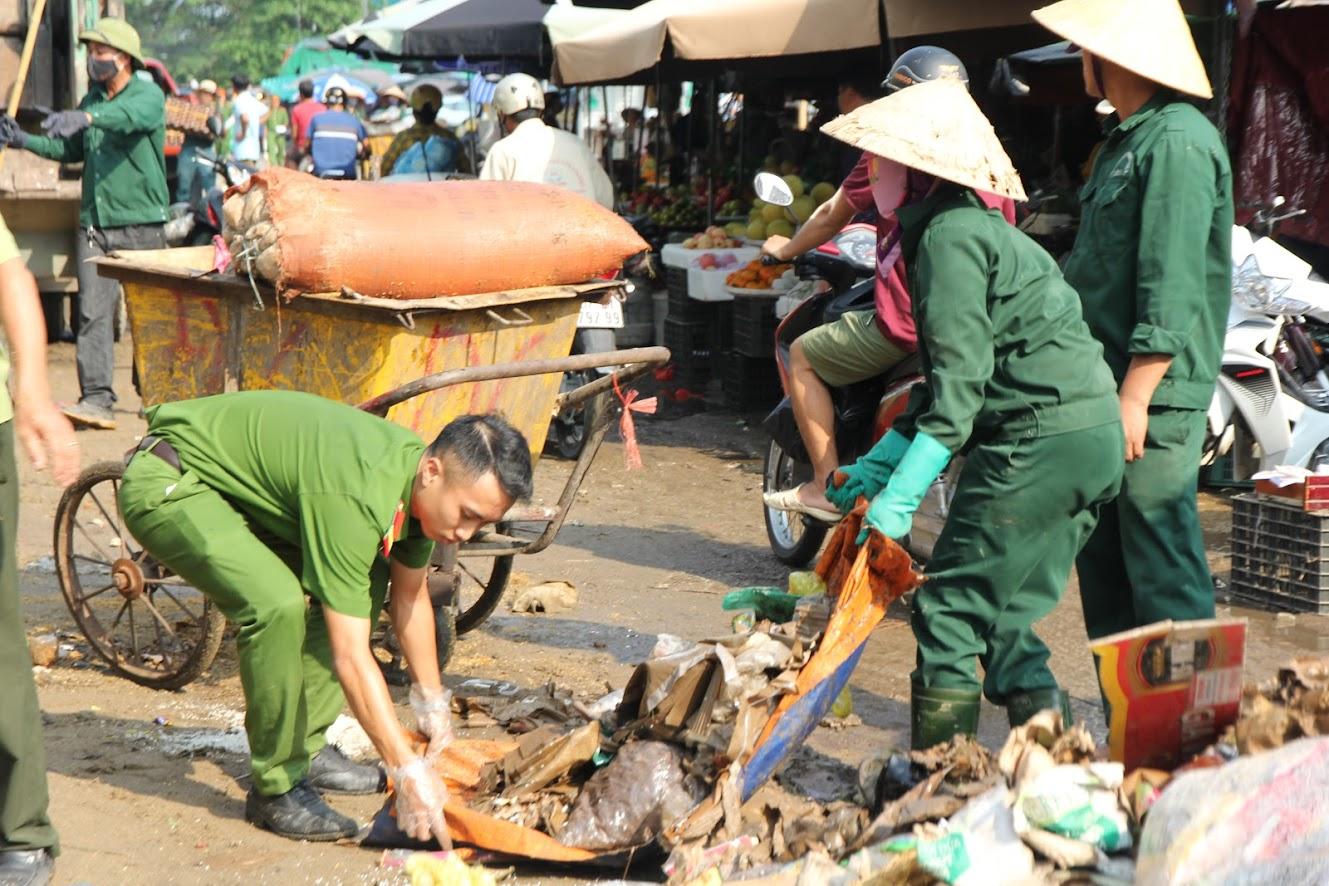 Công an phường Hồng Sơn cùng công nhân vệ sinh môi trường thành phố Vinh dọn dẹp hàng chục tấn rác thải phía trước chợ Vinh. (ảnh: Đức Vũ)