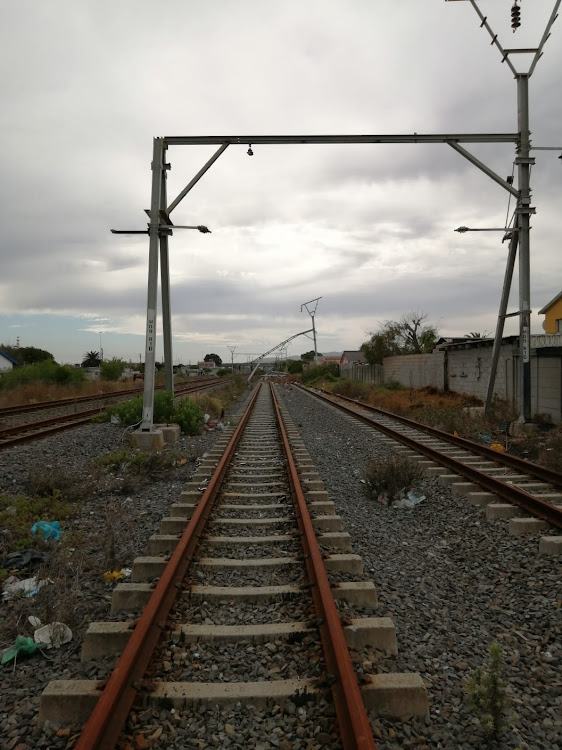 Electric cable masts lie across the tracks in Bonteheuwel, where looters are systematically stealing the remnants of Cape Town's central line.