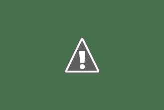Photo: Vi står utenfor musikkpaviljongen og får høre om badstuhuset og kjærlighetsøya i bakgrunnen
