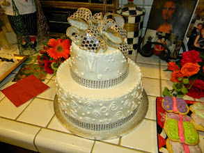 "Photo: Engagement Shower cake: swirls & dots on bottom tier w/3-dot clusters around top. Silver diamond wrap & silver French ribbon bow topper. Initial ""M"" in front."