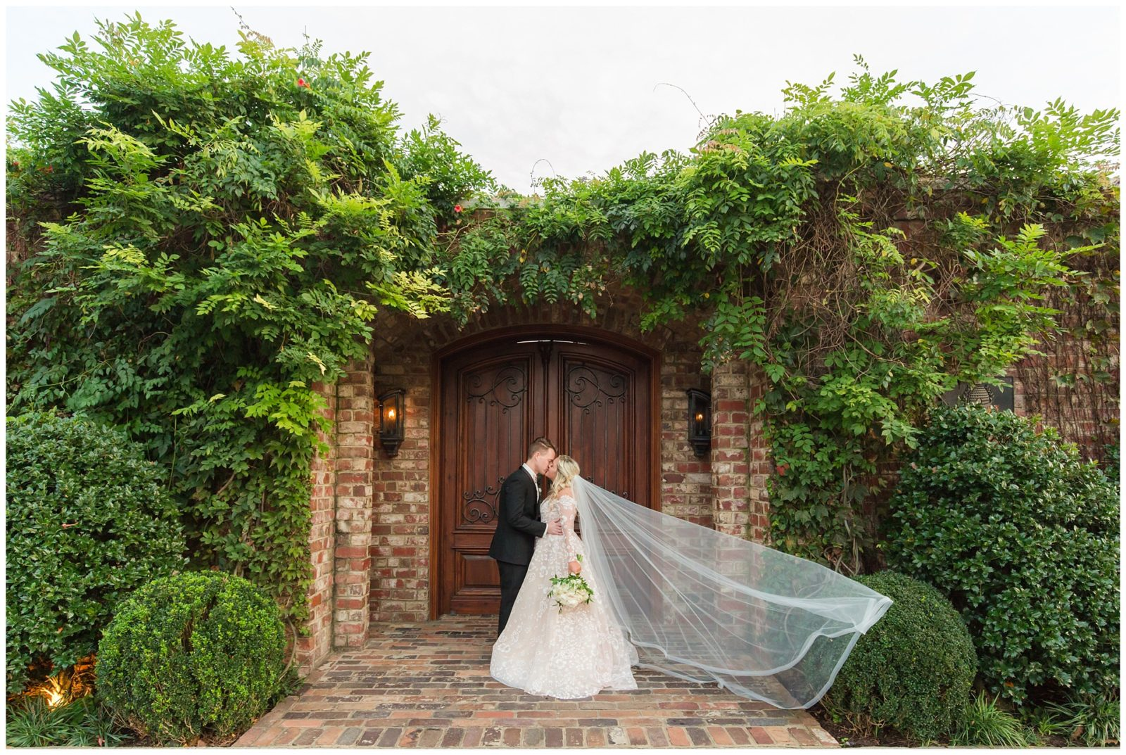 small wedding venue garden gate with newly weds kissing