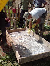 Photo: boris cleaning our first lump of lime dragged from the low pit with a scoop on a broom handle