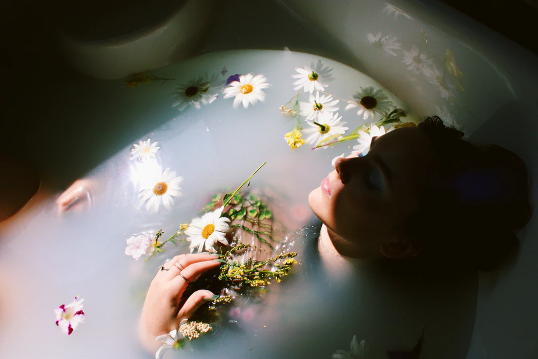 woman in milk bath with white flowers