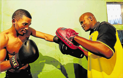 LEFT TO SHOW HIS WILES: Azinga Fuzile working the mitts with trainer Mzamo Chief Njekanye in their rundown Million Dollar boxing gymnasium in Gompo. The pair recently won the prospect and the trainer of the year awards respectively Picture: SINO MAJANGAZA