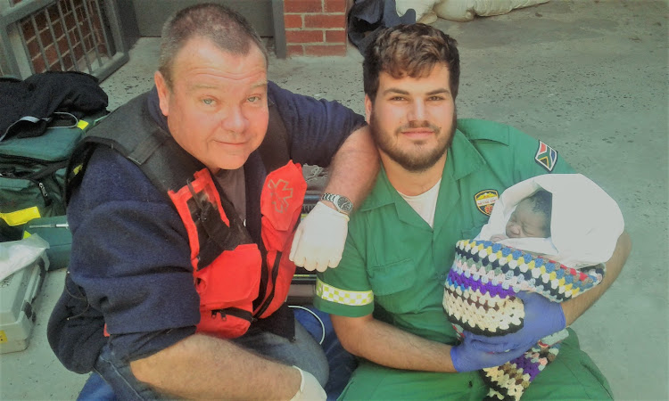Kevin Jones, left, and Fabio Moreira with the baby they helped deliver at Table View Police Station on Thursday morning.