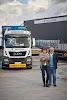 man en vrouw voor een vrachtwagen naast het bedrijfspand