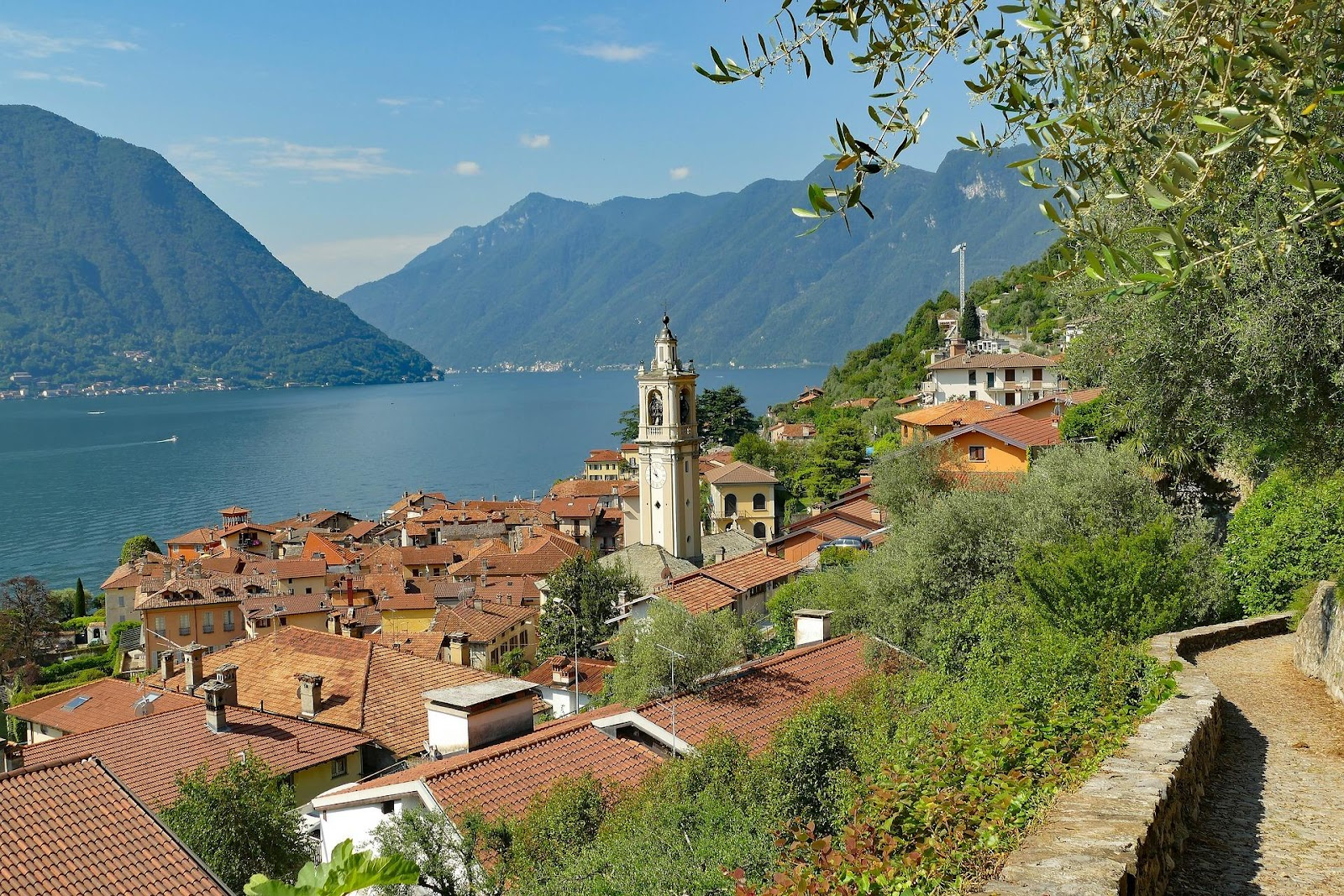 traditional medieval italian hillside village overlooking lake como blue water surrounded by mountains on a clear day