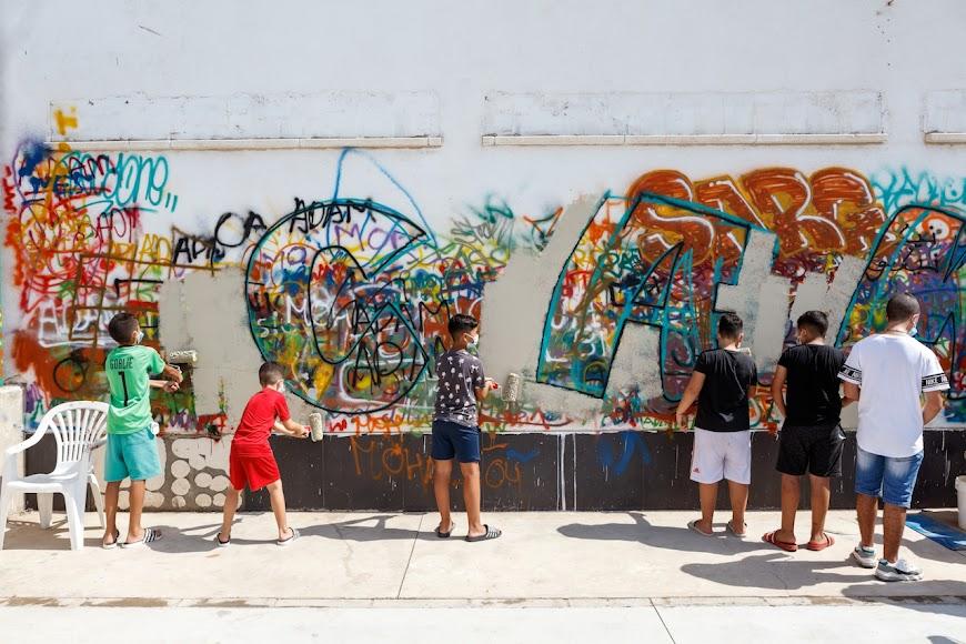 Jóvenes de El Puche realizando un grafiti con la palabra Cambio.