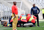 Abbubaker Mobara of Cape Town City FC injured as Benni McCarthy (Head Coach) looks on during the Absa Premiership match between Cape Town City FC and Golden Arrows at Cape Town Stadium on September 22, 2019 in Cape Town, South Africa.