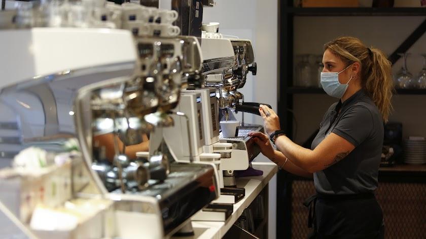 Una camarera sirviendo café en un bar de Granada.