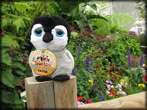 """Photo: Shows off his """"1st visit"""" button in the butterfly garden at Epcot."""