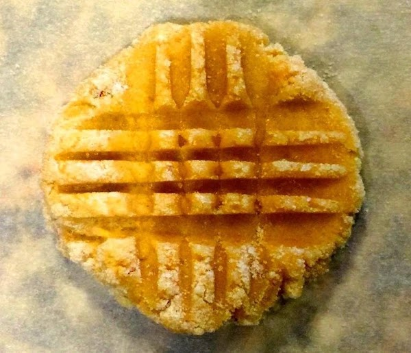 Using a fork, press balls in a crisscross pattern, flattening each cookie to a...