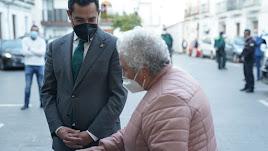 Juanma Moreno charla con una mujer, ambos con la mascarilla puesta, en una imagen de archivo.