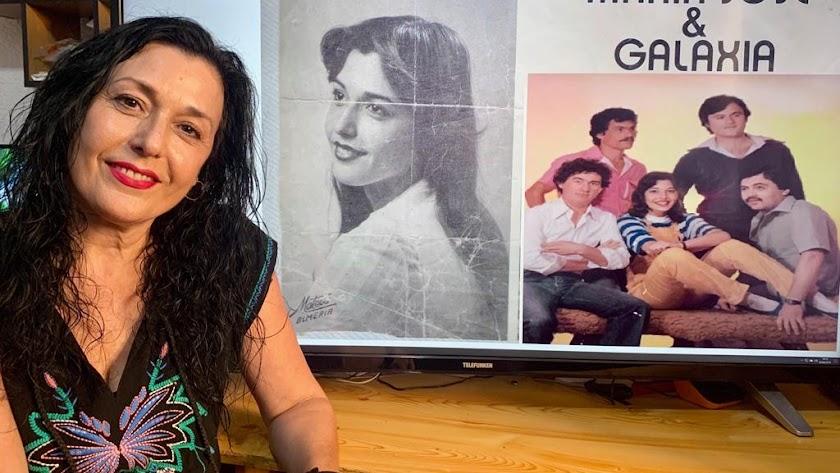 María José Gil  ante un cartel anunciador de la orquesta María José y Galaxia.