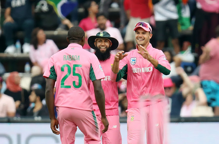 South Africa players Kagiso Rabada (L), Hashim Amla (C) and Aiden Markram (R) celebrate after dismissing Hardik Padya of India during the 2018 Momentum 4th ODI International Series match between the Proteas and India at Wanderers Stadium, Johannesburg South Africa on 10 February 2018.