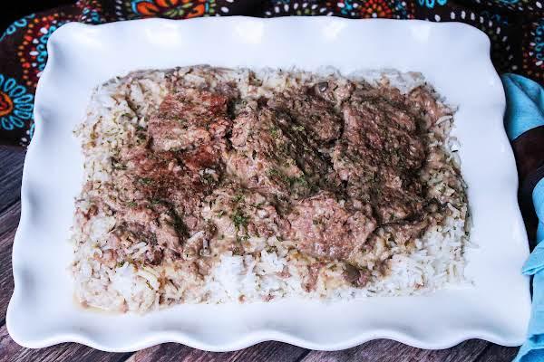 A Platter Of Crock Pot Cube Steak & Gravy With Rice Ready To Serve.