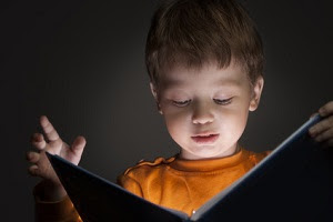 little boy reading magical book