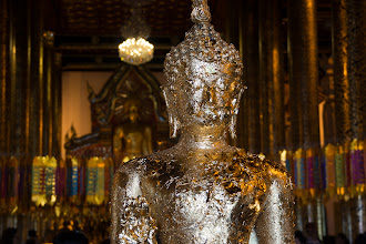 Photo: One can buy squares of gold foil and affix them to this statue, which stands near the entrance of the temple.