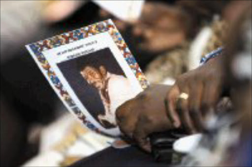 CARING: A family member holds the programme for Sam 'Bra Darkie' Williams' memorial service, held at Baseline, in Newtown, Johannesburg. The acting died of diabetes. Pic. Thobeka Ndabula. 28/02/07. © Sowetan.