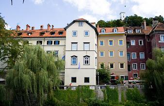 Photo: Hostellini Ljubljanica joen rannalla. Taustalla näkyy Ljubljanan linnantorni.