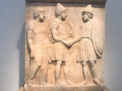 Funerary-Relief-of-Sosias-and-Kephisodoros.jpg -   Funerary relief created at the end of the Peloponnesian War depicts two citizen soldiers from Athens armed with large round shields, lances and pilos helmets. It dates to 410 B.C. at the Altes Museum in Berlin.