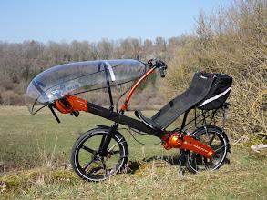 Photo: Vu d'ensemble, Greenmachine electrique monobras orange . Siège Mesh (toile) avec technologie spécial Flevobike pour une tension et une aérationoptimal.