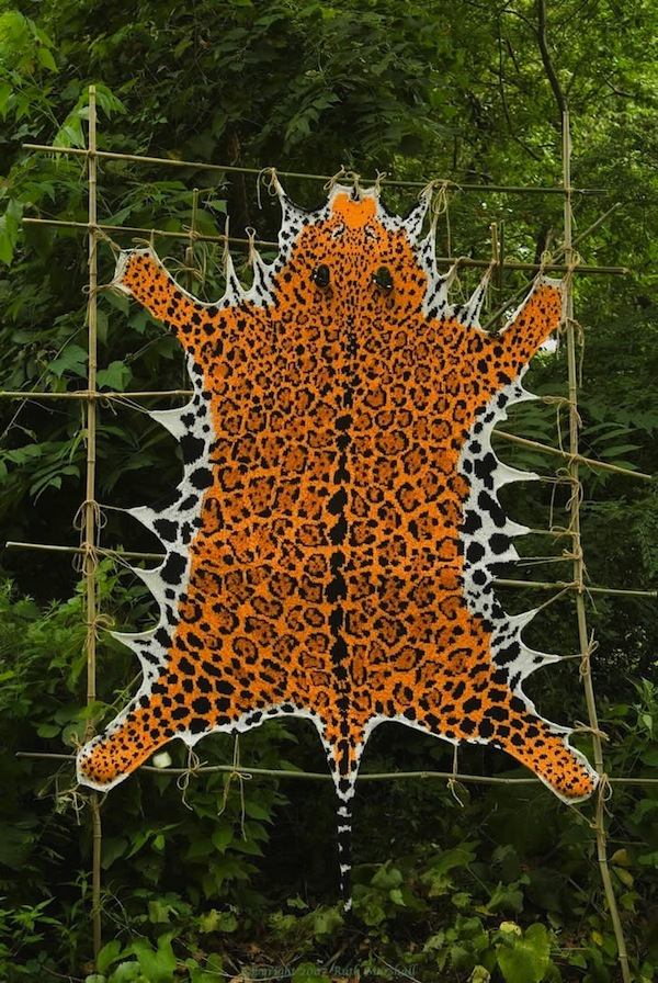 "Photo: Golden Jaguar 2007 81"" x 51"", (2.05m x 1.3m) Hand knitted textile.  Yarn, string, sticks. Designed from generic images. (C)Ruth Marshall, 2007."