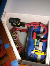 Photo: Locker under nav station seat contains starter battery, battery & bilge pump management panel, and automatic charge relay (ACR) for start battery.
