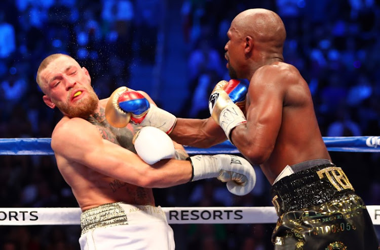 Floyd Mayweather teaches Connor McGregor how to take a punch. Picture: REUTERS