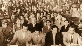 Περιγραφή: Μάης του 1960: Εγινε η «Μεγάλη Δίκη» στο Στρατοδικείο Αθηνών. Ο Χαρίλαος Φλωράκης στο κέντρο της δεύτερης σειράς με το σκούρο κοστούμι