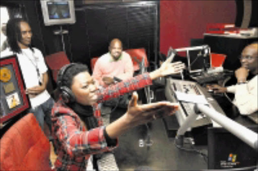HONOURED: Lira is overcome with emotions at Kaya FM studios. With her are the station's MD Greg Maloka and T-Bose. Pic: Antonio Muchave. 04/06/2009. © Sowetan