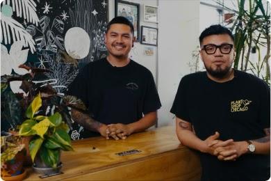 Dos hombres con camisetas negras en la recepción de su tienda de plantas.