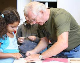 Photo: Ome Herman begeleidt de figuurzaagclub. Waar kan jong en oud zich technisch en gezellig nog zo uitleven?