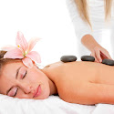 A lady with a flower in her hair receiving a hot stone massage