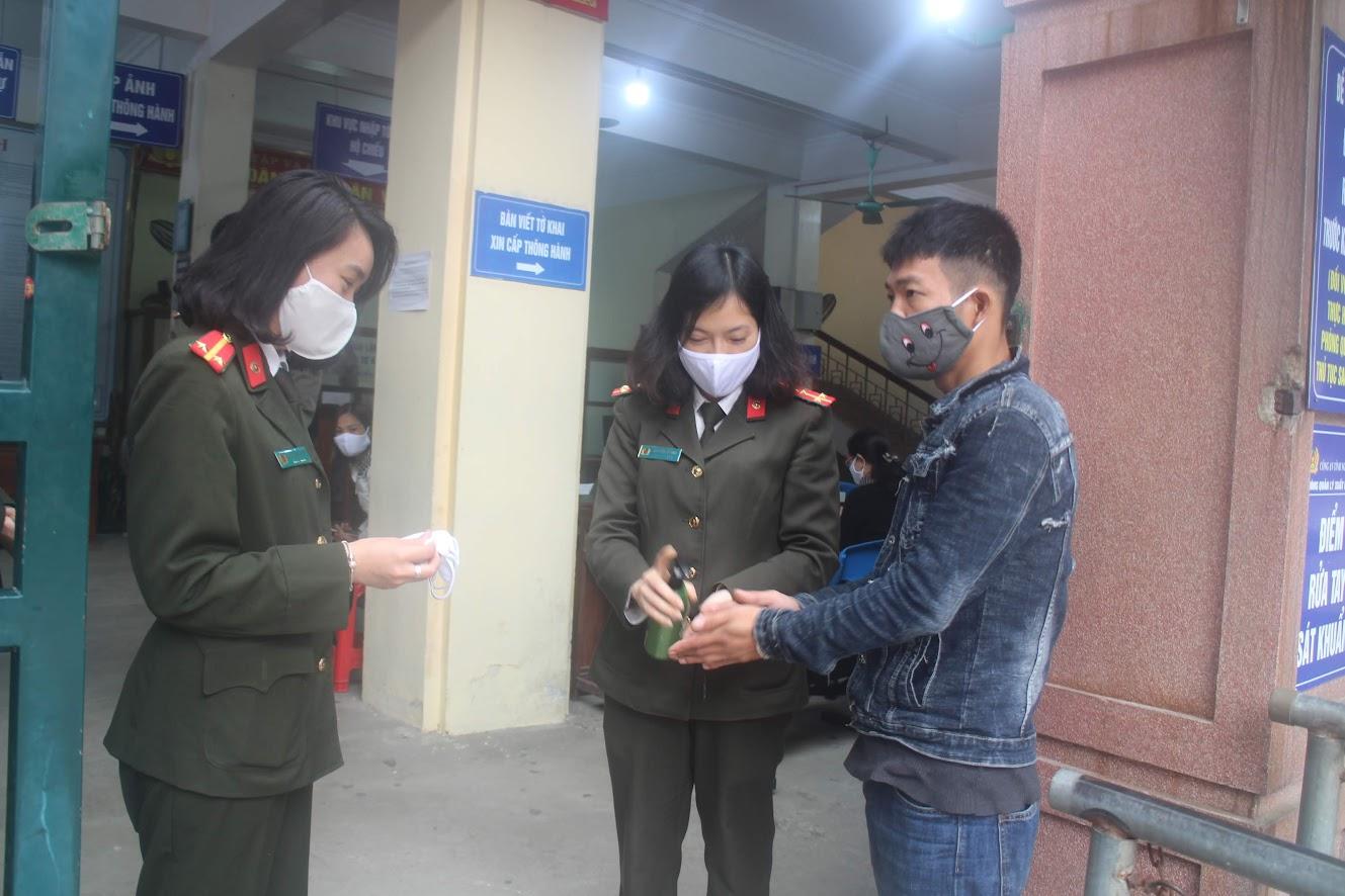 Cán bộ Phòng Quản lý xuất nhập cảnh phát tặng khẩu trang kháng khuẩn và yêu cầu công dân rửa tay sát khuẩn trước khi vào làm thủ tục
